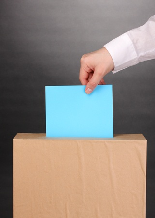Hand with voting ballot and box on grey background Stock Photo - 13580280