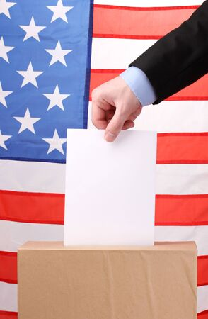 Hand with voting ballot and box on Flag of USA photo