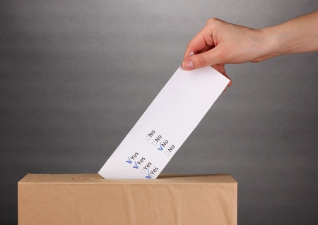 Hand with voting ballot and box on grey background photo