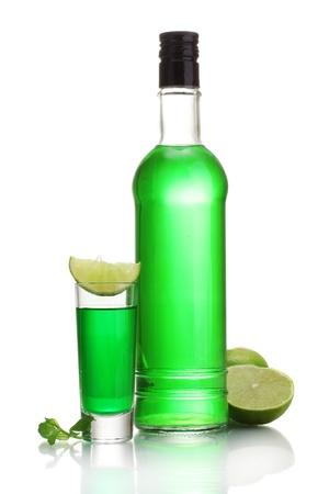ajenjo: botella y un vaso de absenta con cal aislado en blanco Foto de archivo