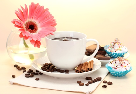 cappuchino: cup of coffee and gerbera, beans, cinnamon sticks on wooden table