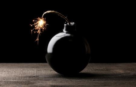 Cartoon style bomb on wooden table on black background Stock Photo - 13581424
