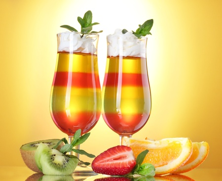 fruit jelly in glasses and fruits on yellow background