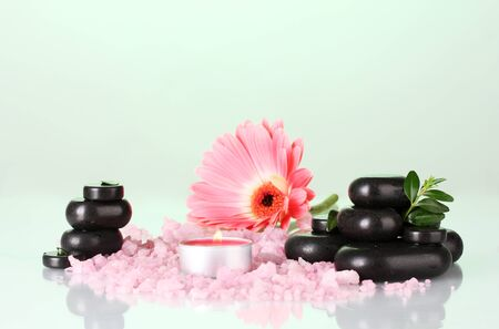 Composition of spa stones and bath salt on colorful background photo