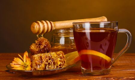 honey, lemon, honeycomb and a cup of tea on wooden table on brown background Stock Photo - 13666679