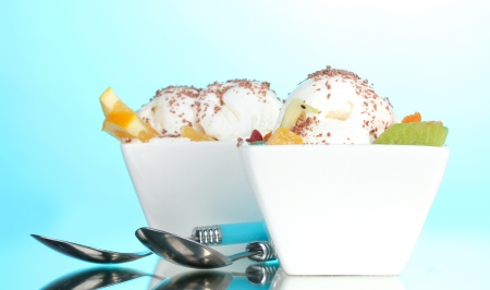 delicious vanilla ice cream with chocolate and fruits in bowls and spoons on blue background photo