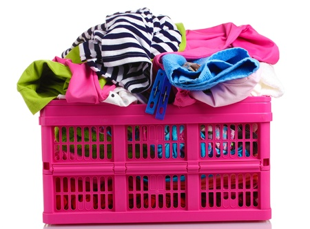 Clothes in pink plastic basket isolated on white photo