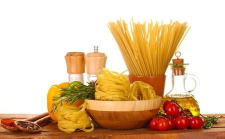 spaghetti, noodles in bowl, jar of oil and vegetables on wooden table isolated on white photo