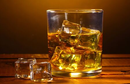 glass of whiskey and ice on wooden table on brown background Stock Photo - 13666754
