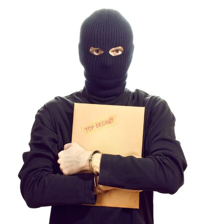 Bandit in black mask in handcuffs with top secret envelope isolated on white Stock Photo - 13664413