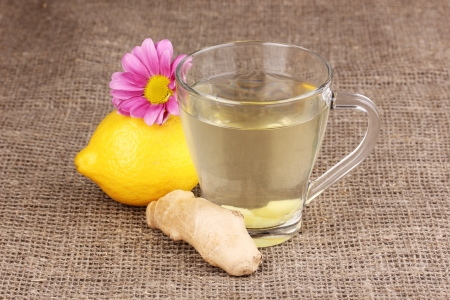 Healthy ginger tea with lemon and flower on sackcloth photo