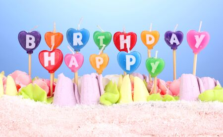 Birthday cake with candles on blue background photo