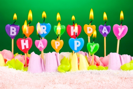 Birthday cake with candles on green background photo