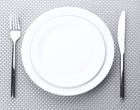 White empty plates with fork and knife on a grey tablecloth photo