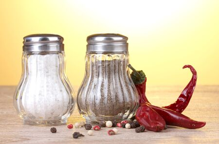 Salt and pepper mills and spices on wooden table on yellow background photo