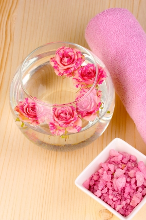 Vase with roses, spa setting on wooden background photo
