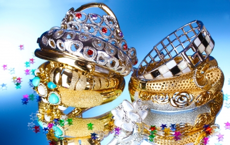 jewelleries: Beautiful silver and gold bracelets and ring on blue background