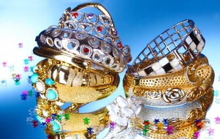 Schöne Silber-und Gold-Armbänder und Ring auf blauem Hintergrund