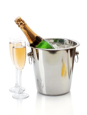 Botella de Champagne en un cubo con hielo y vasos de champán, aislado en blanco
