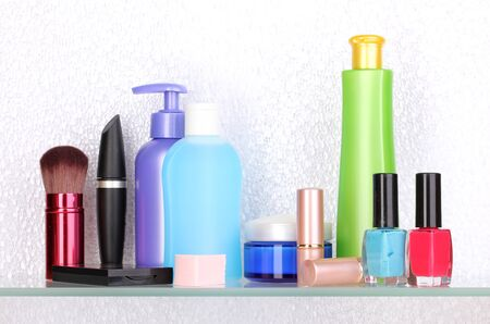 Shelf with cosmetics and toiletries in bathroom photo