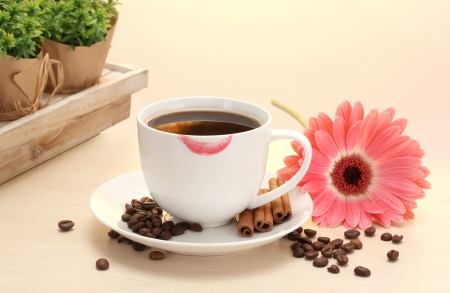 cup of coffee with lipstick mark and gerbera beans, cinnamon sticks on wooden table photo