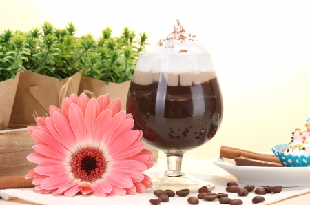 glass of coffee cocktail and gerbera flower on wooden table photo