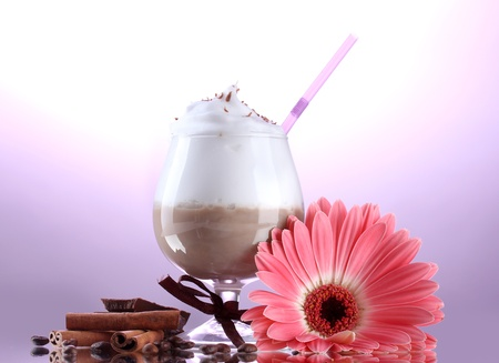 glass of coffee cocktail and gerbera flower on purple background photo