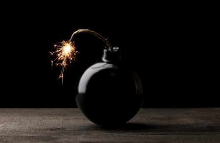 detonate: Cartoon style bomb on wooden table on black background Stock Photo