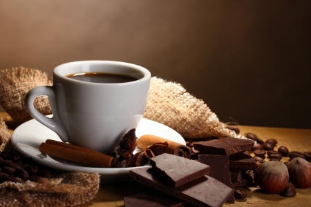 coffee cup and beans, cinnamon sticks, nuts and chocolate on wooden table on brown background Stock Photo - 13680919
