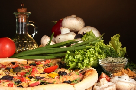delicious pizza, vegetables and spices on wooden table on brown background Stock Photo - 13796643