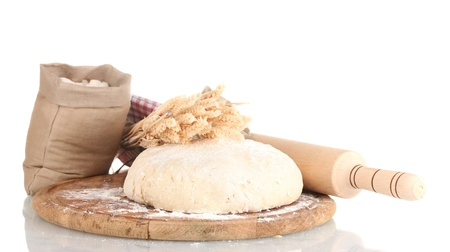 Dough and bags with flour on wooden board isolated on white Stock Photo