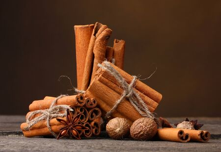 Cinnamon sticks, nutmeg and anise on wooden table on brown background photo