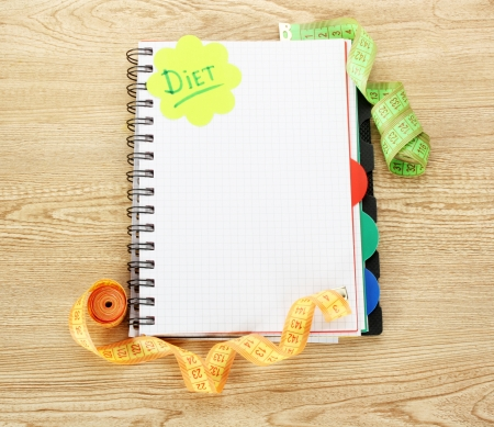Planning of diet. Notebook measuring tapes and pen on wooden table Stock Photo - 13793401