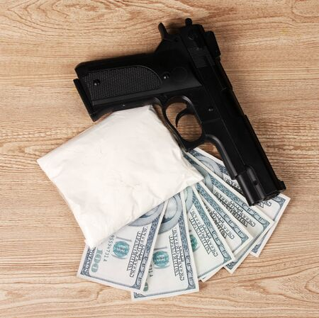 Cocaine in package, dollars and handgun on wooden background photo