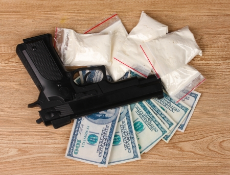 Cocaine in packages, dollars and handgun on wooden background photo