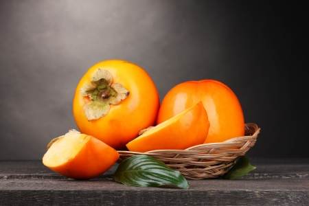 Appetizing persimmons in pad on wooden table on grey background photo