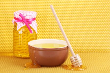 Jar of honey, bowl and wooden drizzler with honey on yellow honeycomb background  photo