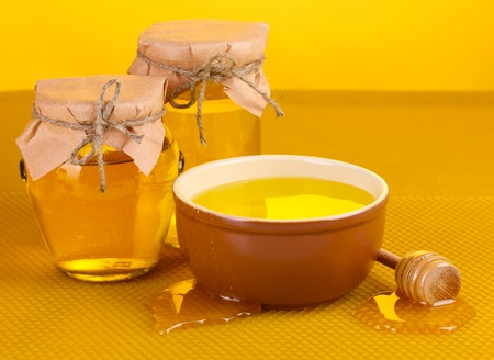 Jars of honey, bowl and wooden drizzler with honey on yellow honeycomb background  photo