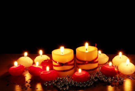 Beautiful candles and decor on wooden table on black background photo