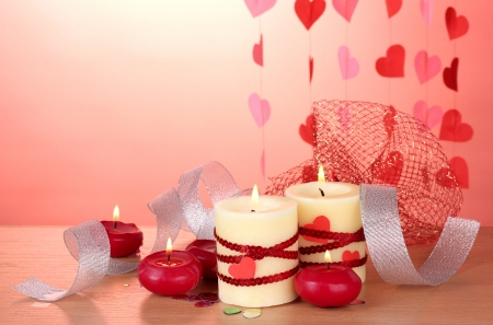 candles for Valentines Day on wooden table on red background photo