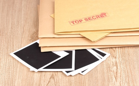 Envelopes with top secret stamp with photo papers close-up on wooden background Stock Photo - 13796814