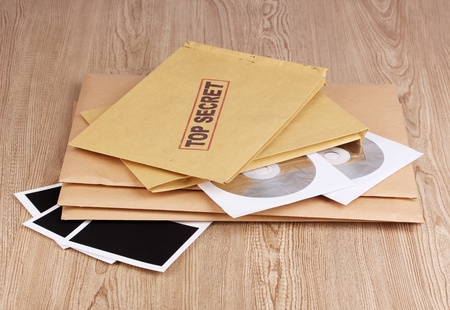 Envelopes with top secret stamp with photo papers and CD disks on wooden background photo