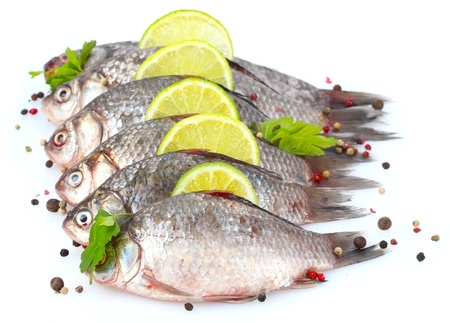 Fresh fishes with lime, parsley and spice isolated on white photo