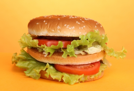 Big and tasty hamburger on yellow background photo