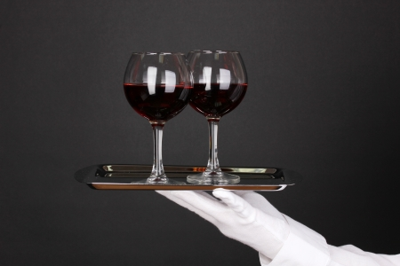 Hand in glove holding silver tray with wineglasses isolated on black photo