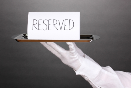 Hand in glove holding silver tray with card saying reserved on grey background Stock Photo