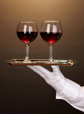 Hand in glove holding silver tray with wineglasses on brown background photo