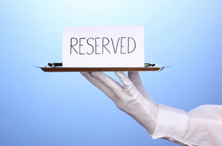 Hand in glove holding silver tray with card saying reserved on blue background