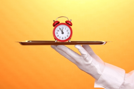 Hand in glove holding silver tray with alarm clock on yellow background photo