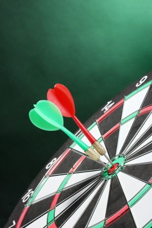 dart concept: dart board with darts on green background